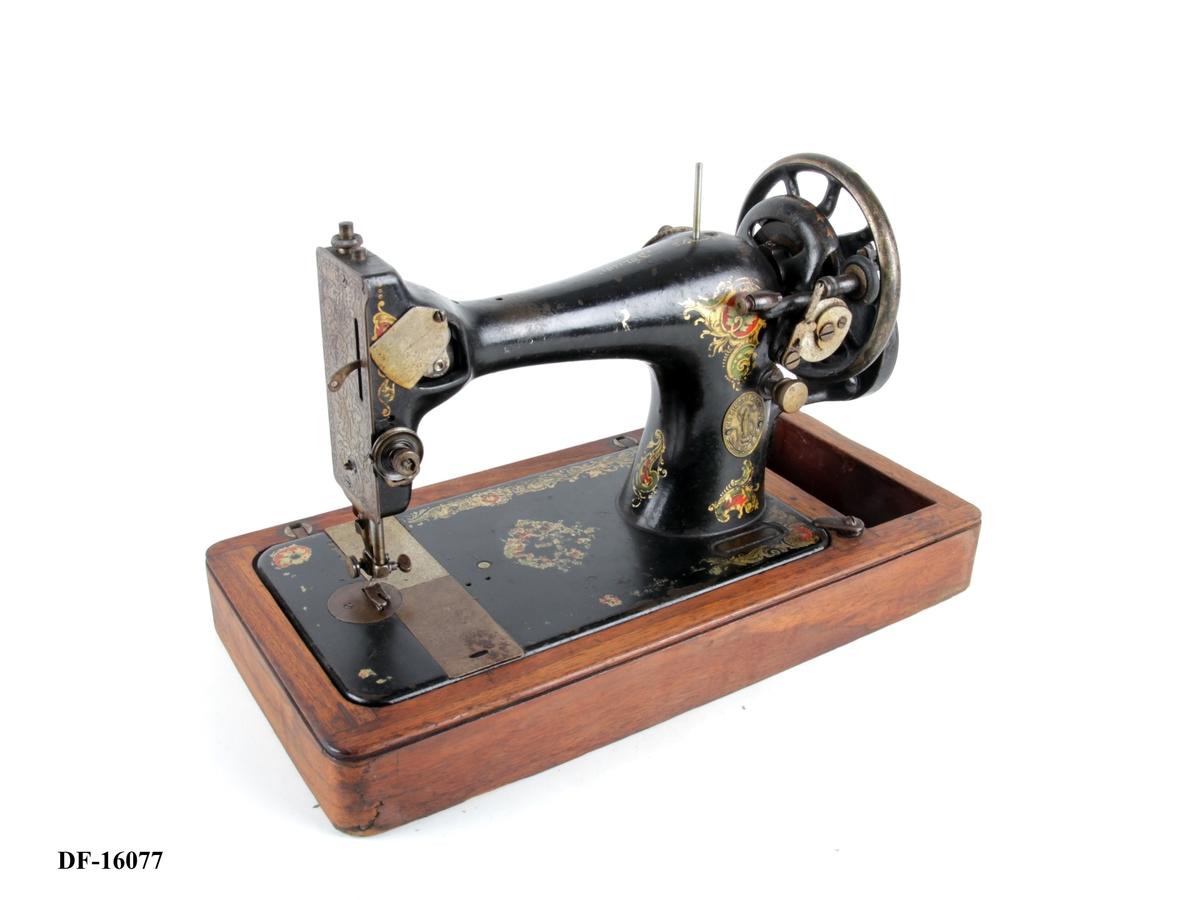 Symaskin på tresokkel. En spole, spoleverk og håndsveiv. Snellerom integrert i tresokkelen. Gulldekor.