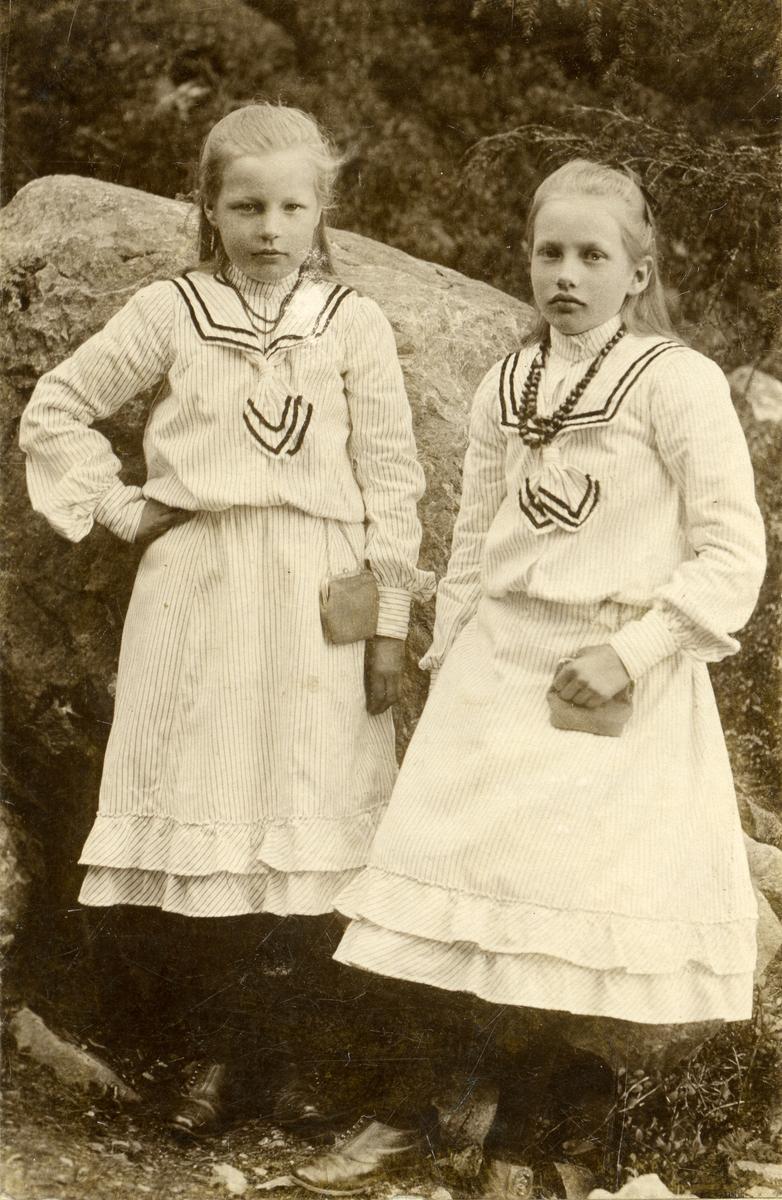 To jenter står foran en stein. Jentene er begge iført hvite kjoler med krager. Begge har halssmykke og en liten veske.