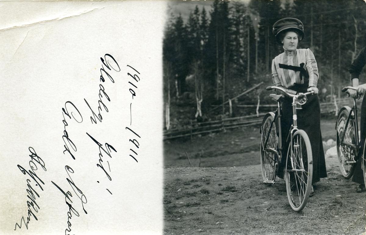 Prospektkort av Anna Bergsund som står ved en sykkel. Tatt ca. 1910.