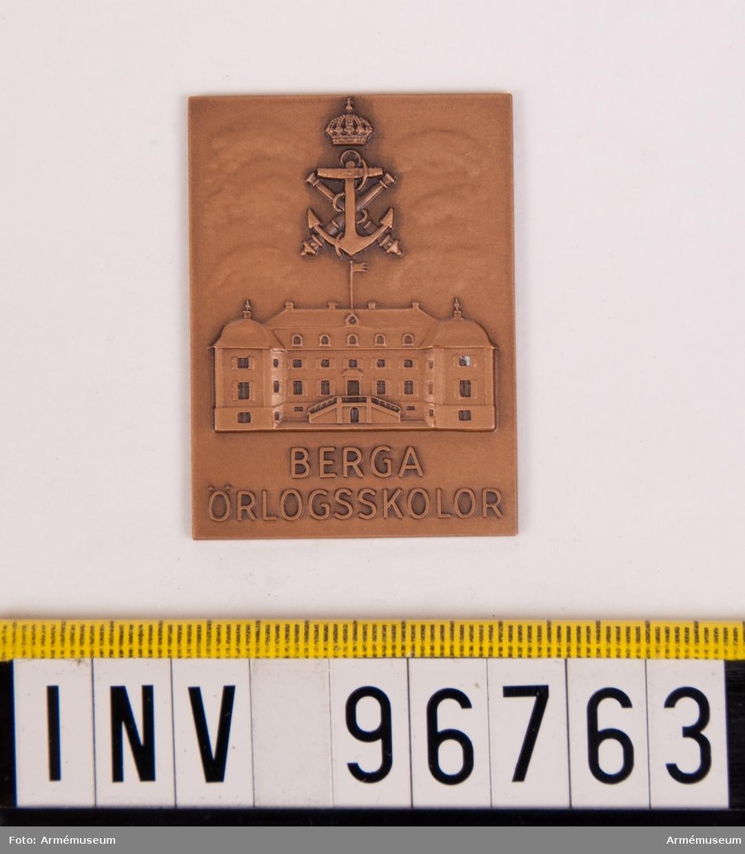 Plakett i brons för Berga örlogsskolor. Plakett, åtsida upptagande exteriör av Berga slott jämte marinemblemet ankare, kanoner och kungl. krona samt inskr. BERGA ÖRLOGSSKOLOR. Stans nr 2142. Stans härdad 1960-09-05.