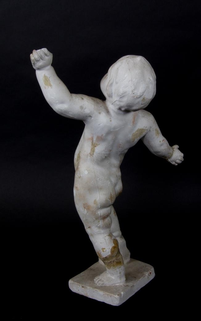 Stående putto i helfigur med utbredda armar. Ena benet stödjer sig på en sten.