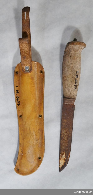 Tollekniv med treslire. 6 stk nagler som fester hempe til slira. Slira er dekorert med svipenn og maling. Kniven med svipenn.