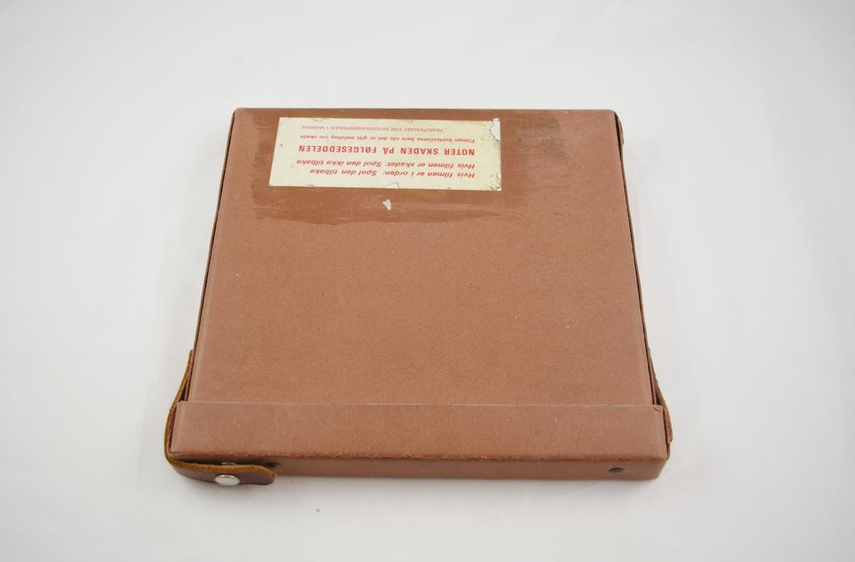 Filmrull i eske. Film på metallspole. Firkantet papiretui åpnes langs en av sidekantene, festes med metallspenne.