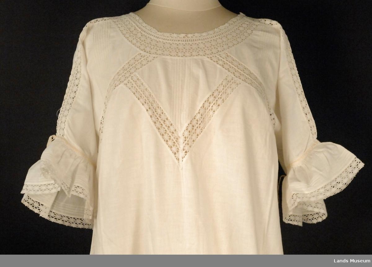 Dekorert med biser, blonder og smale gule silkebånd. Kort erme med kappe. Utskrådd kjole med kiler i sidene nederst.