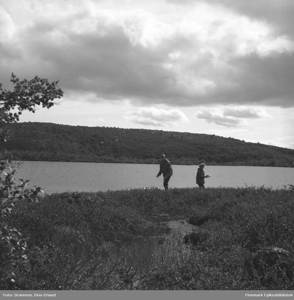 To personer på fisketur ved bredden av et fjellvann. Personene er ukjent.