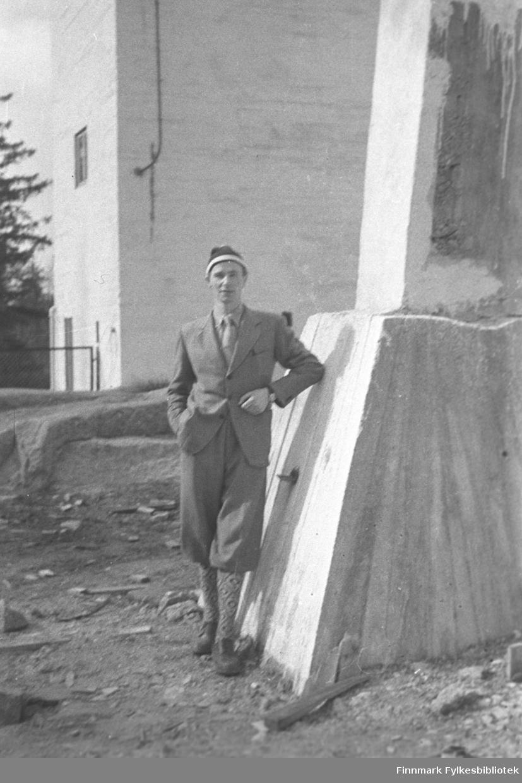 En mann, muligens Eino Drannem, poserer ved et fundament ved kraftverket i Pasvik.