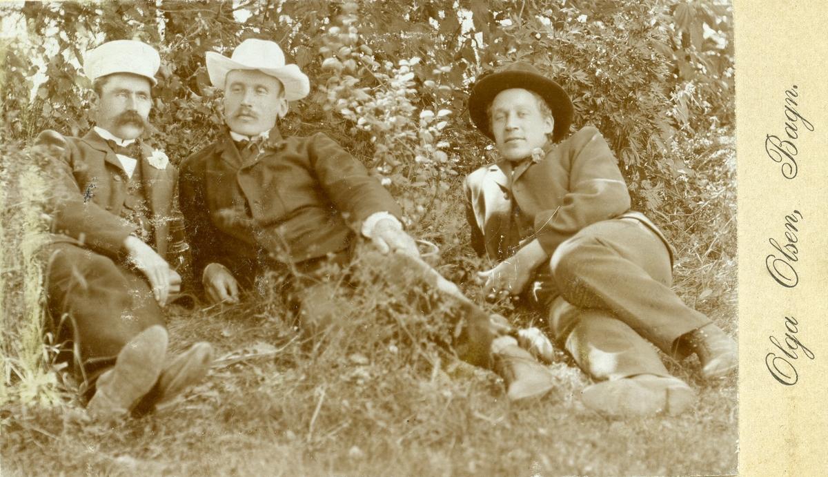 Portrett av Hans, Olaus og Ola Islandsmoen liggende i gresset, alle med hatt på hodet.