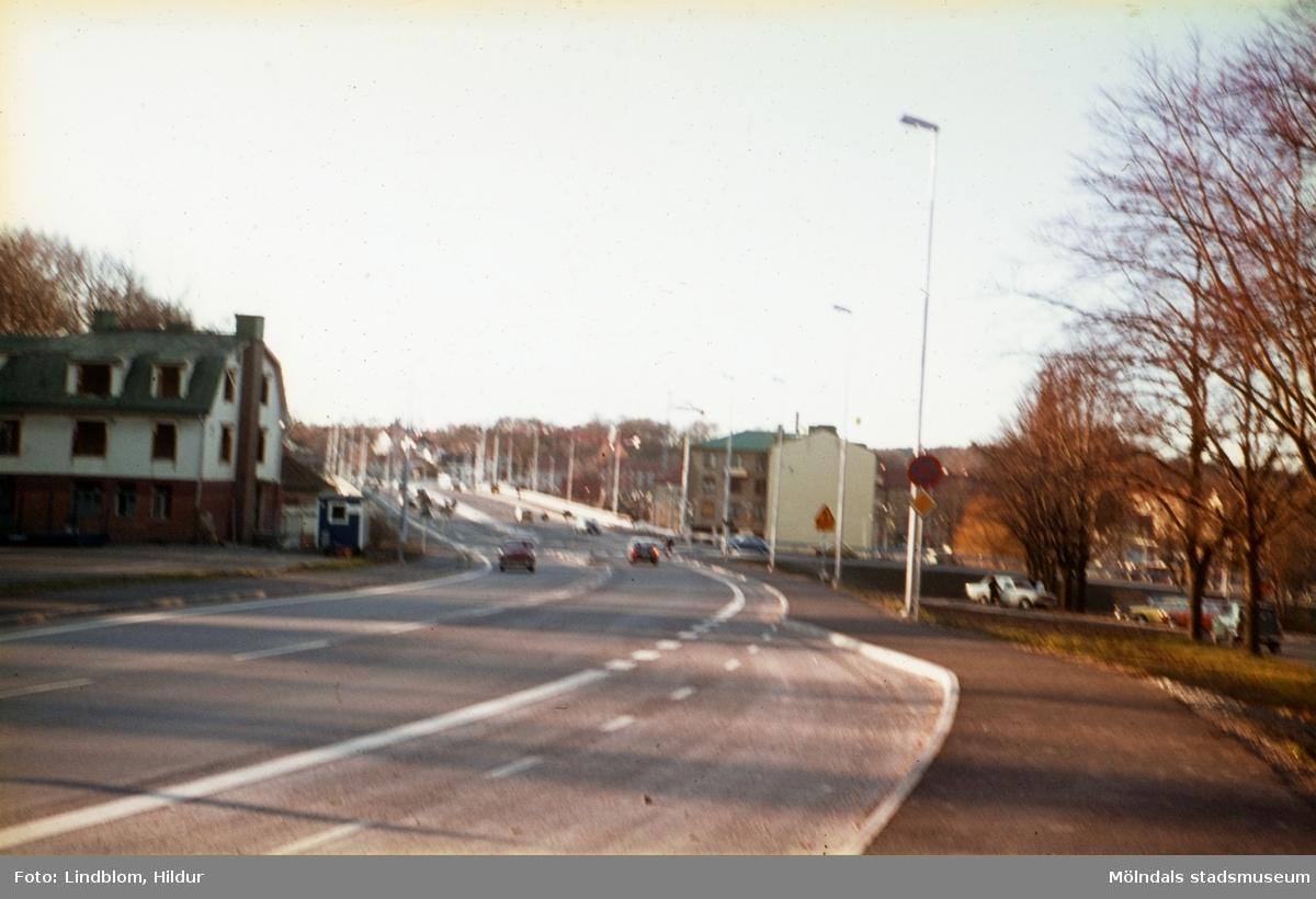 Vy från Kvarnbygatan mot Mölndals Bro i Mölndal, 1970-tal (efter 1975). Till vänster ses Restaurant Godhem med adress Kvarnbygatan 13. I mitten till höger om bron ses huset Kvarnbygatan 1.  För mer information om bilden se under tilläggsinformation.