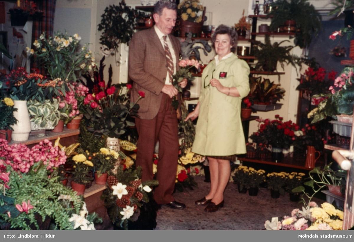 En man och en kvinna fotograferade i blomsteraffären vid Gamla Torget i Mölndal med adress Kvarnbygatan 45, 1970-tal. Kvinnan hette Kerstin och var ägare av affären. Lokalen används numera av Corpus Pizzeria.  För mer information om bilden se under tilläggsinformation.