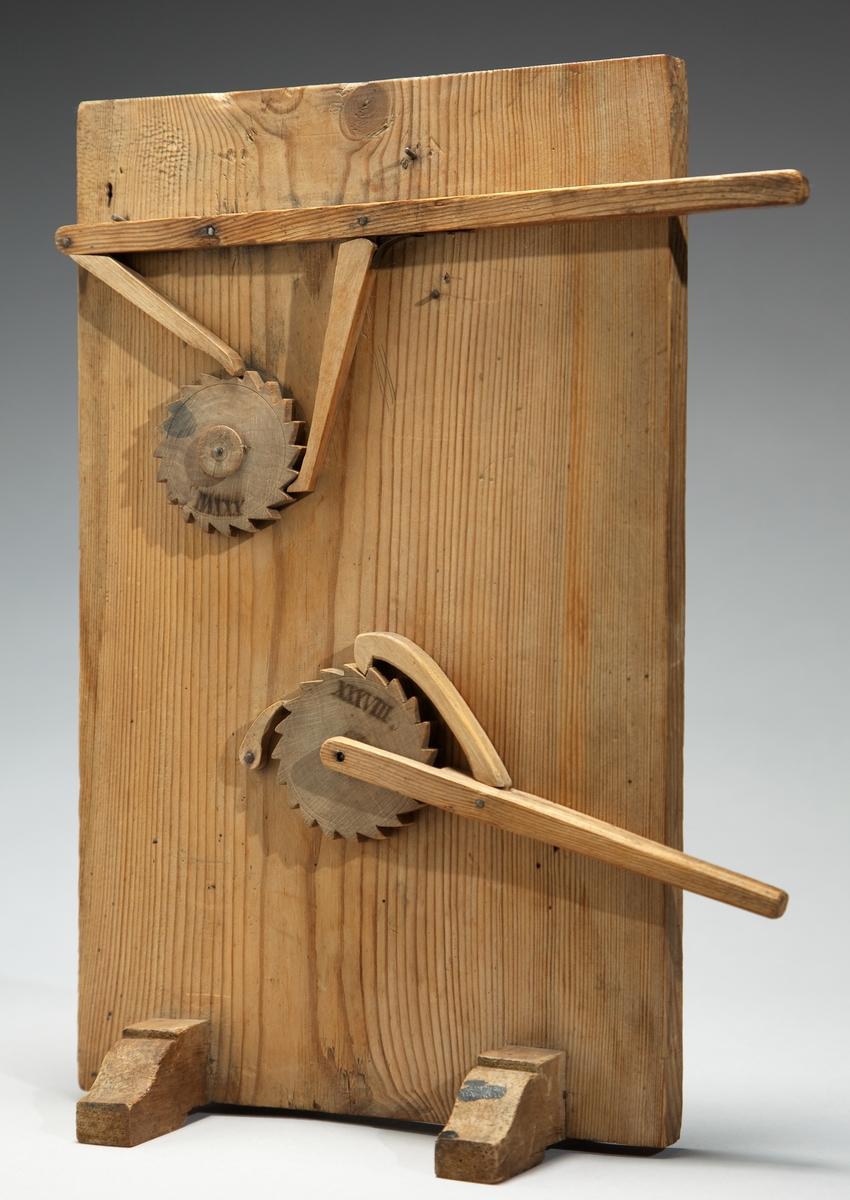 Modell ur Polhems mekaniska alfabet. Text på föremålet: XXXVII, XXXVIII. Med hjälp av en hävstång och dess två hakar erhålles en kontinuerlig rotationsrörelse hos spärrhjulet. Hävstången nedanför, som endast har en hake och en spärr, ger en diskontinuerlig rotationsrörelse.