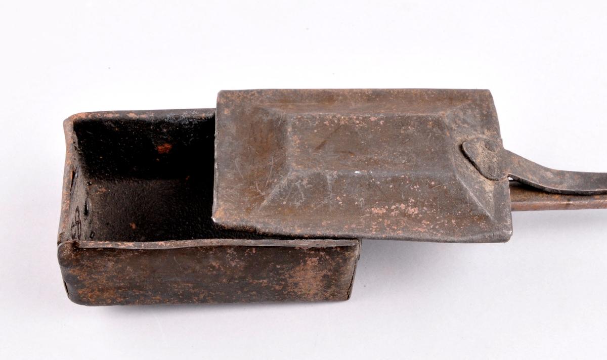 Rektangulær jarnskuff (kammer) med lok til å skreie att og fram. Smidd fast på ei lang stong med trehandtak.