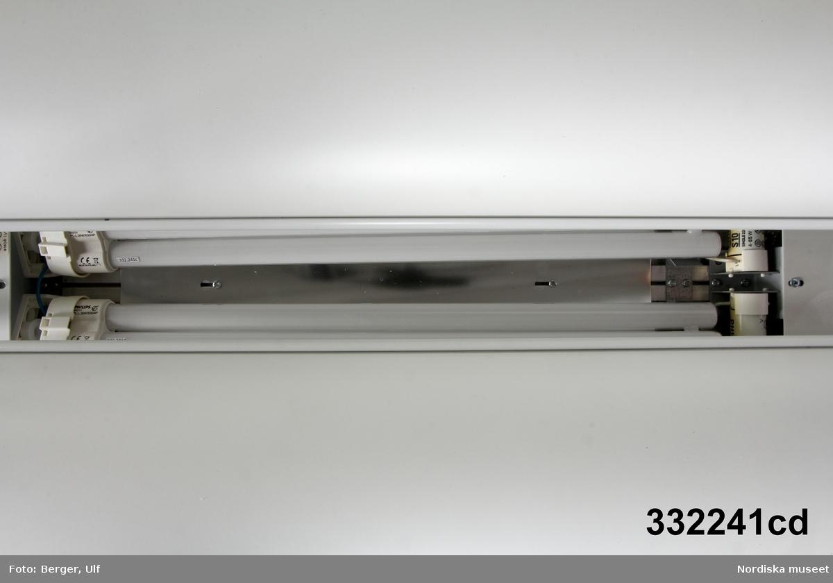 Takpendel i vitlackerad plåt bestående av två stora vitlackerade aluminiumplåtar böjda konvext, liksom utspända vingarna på en fågel. Vingarna hänger i stag som utgår från kortsidorna av en skålformad ränna i vilket två 36 Wolts lysrör är placerade. Tunn perforerad vitlackerad plåt bländskydd ovanför lysrören. Etikett, text se nedan.  Metallstag för takmontering med metalltrådsupphäng vid båda kortsidorna. Vit sladd med jordad stickpropp. /Maria Maxén 2016-03-03