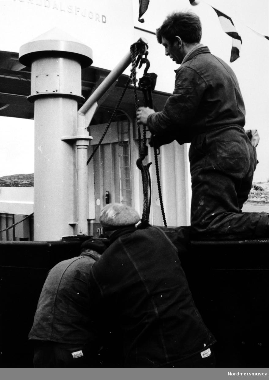"""Bildet viser B/F""""Norddalsfjord"""" Storviks Mek. Verksteds bnr.14 ved piren under utrustning.   """"Norddalsfjord"""" ble levert til Møre og Romsdal Fylkesbåtar 15. mars 1961 og hadde følgende hoveddimensjoner: L 31,20 m x B 8,55 m x D 3,35 m og hadde en tonnasje på 159 bruttoregistertonn. Fremdriftsmaskineriet består av 3 Volvo Penta turboladede dieselmotorer type TMD96 på til sammen 420 hk som via kilremdrift var koblet til et felles gir og propellaksel med vribar propell, slik at hver enkelt av motorene kunne kjøres separat. Fergen hadde 2 Bolinders vekselstrømsaggregater type 1052MG på 23 hk hver tilkoblet en generator på 17 kW. Fergen var utstyrt med elektrohydraulisk styremaskin.  Fergen har plass til 18 personbiler og har sertifikat for 160 passasjerer. Forut er det innredet 6 lugarer for offiserer og restaurantpersonale og akterut en mannskapslugar for 4 personer og toppfarten er 11,4 knop og marsjfarten 10,5 knop.  Ferga er verkstedets første nybygg etter B/F""""Trygge"""" som ble levert i 1938.  Arbeiderne holder på å henge på plass ankeret i ankerlomma. Personene på bildet er øverst platearbeider Kåre Olsen med nikketalja. Personen til høyre med ryggen til er sjauer Sigbjørn Iversen og personen til venstre er ukjent.  Signalflaggene er oppe på fergen.  Bildet er fra 1961. Kilde/tekst: Peter Storvik. Fra Nordmøre museums fotosamlinger."""