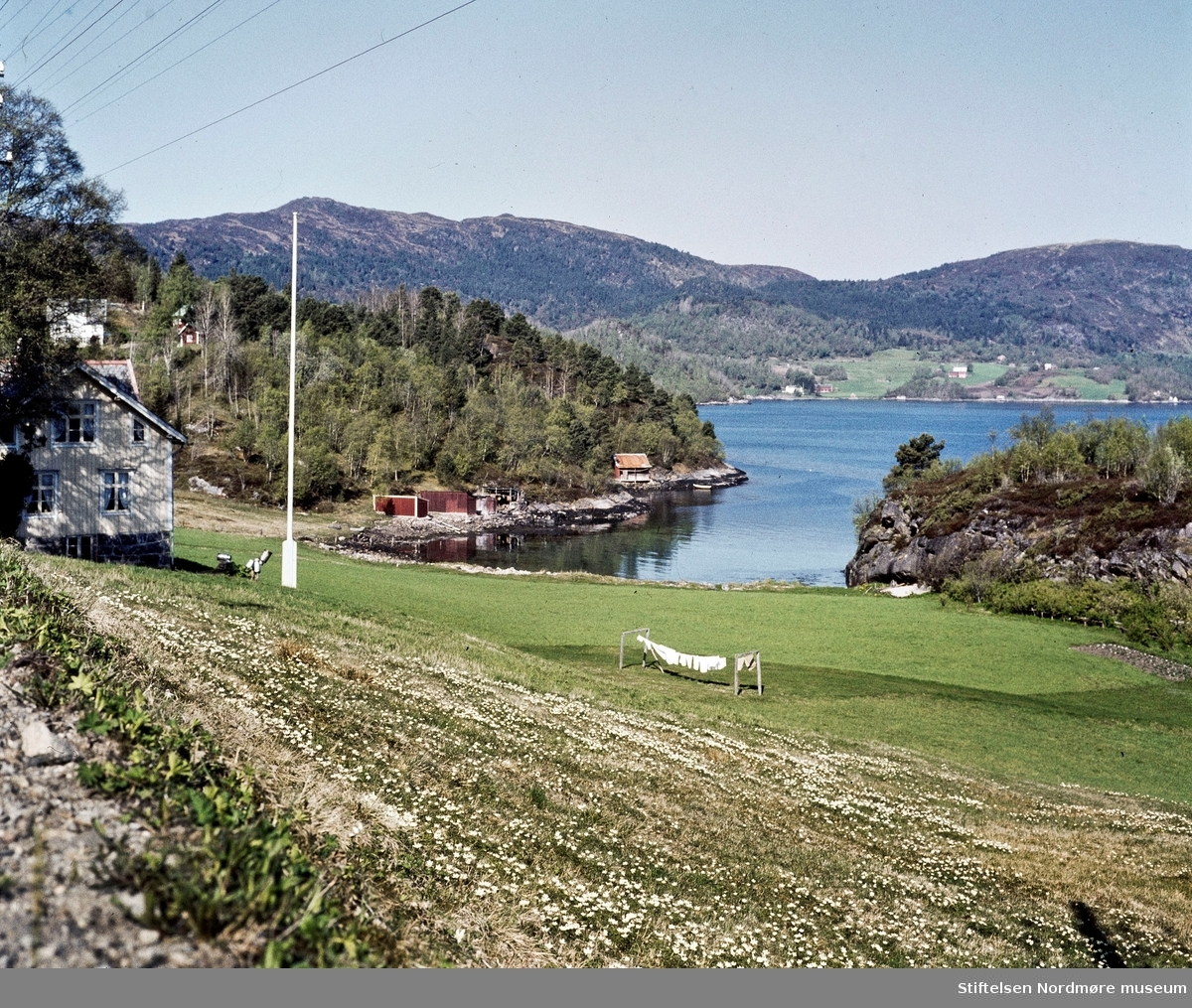 Klesvask, melkespann, tun, landbruk, idyll, gård, fjord, strand. På Freiøya? Portfoliodias fra fotograf Nils Willams sitt arkiv. Nordmøre Museums fotosamlinger.
