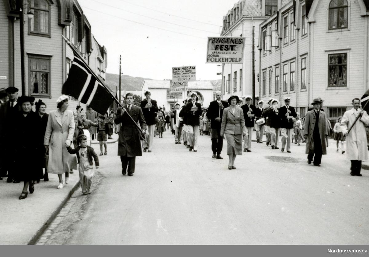 """Dette er etter all sannsynlighet Arbeidernes Musikkorps, eller """"Arbeidermusikken"""" som det het på folkemunne. Tror det er Olaf Wiik som går foran til venstre. Det ble stiftet i 1932 og var aktive frem til 1940 og fra 1951 til 1955. """"Gjenoppsto"""" som Kristiansund Ungdomskorps i 1961 og lagt ned i 1999. (info: Øyvin Dall-Larsen 2017).  Paradetog på vei opp Clausens gate. fra Lars Guttormsens gate på Kirkelandet i Kristiansund, ledet an av musikkorps og med folk bærende på plakater for Norsk Folkehjelp. Muligens et 1. maitog - Arbeidernes internasjonale kampdag? Kan være fra perioden 1955 til 1965. Fotograf kan være Erling Norman Winje. Fra Nordmøre museums fotosamlinger. - Dette er ikke Magnus Blikstadsgate, men nederst i Clausensgate. (Tilleggsinfo: Kari F. Lader.)"""