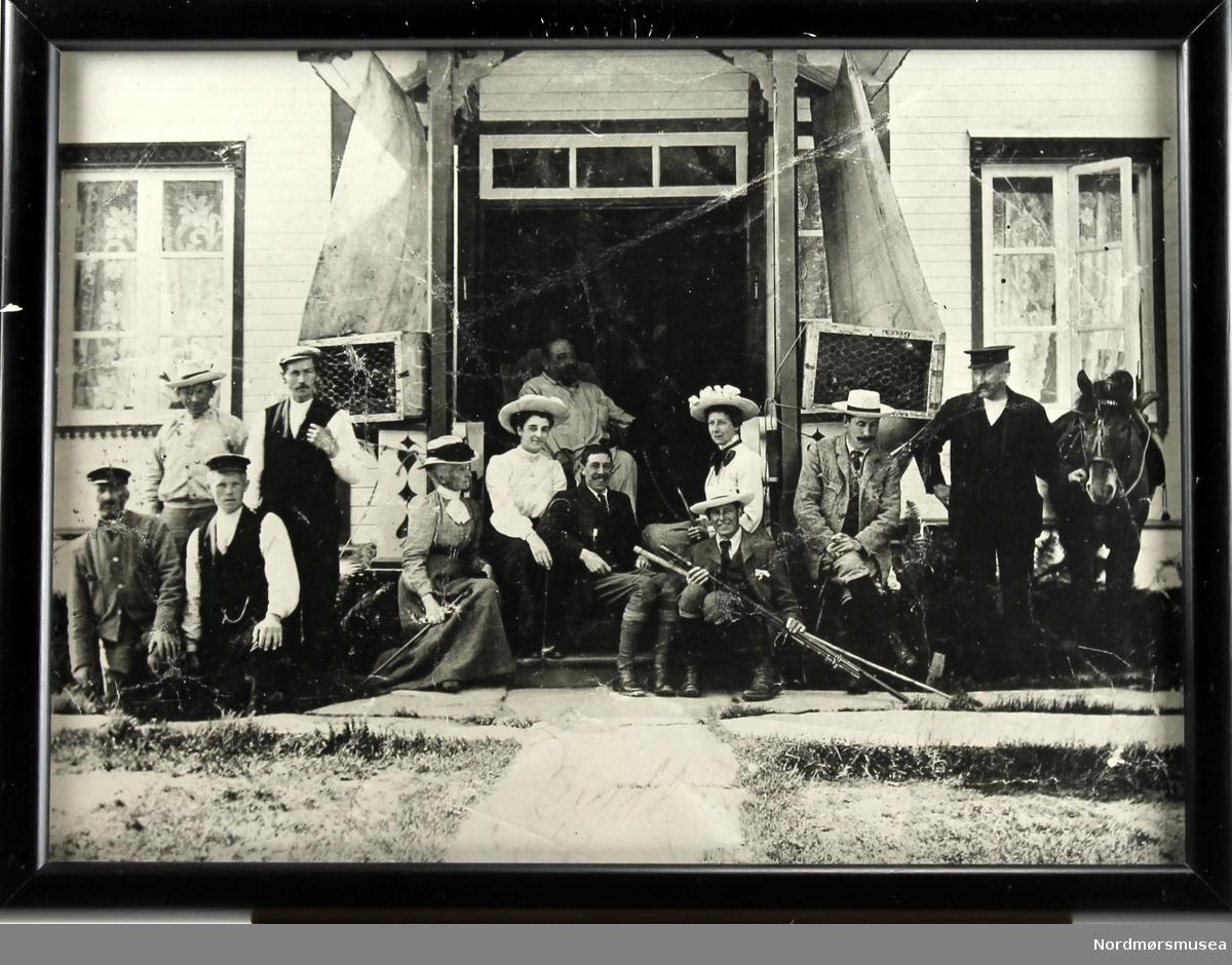 Motivet er et arrangert gruppebilde ved inngangspartiet på Gulla Gård. Sentralt i bildet er Fleetwood Sandeman, som sitter i en stol foran inngangsdøren. Til høyre i bildet står en mann med hest, og på begge sider av inngangspartiet ser vi kasser med høns/fugl. En mann holder en fiskestang, noen holder gevær. Det er sommer, og bildet har en humoristisk tone.