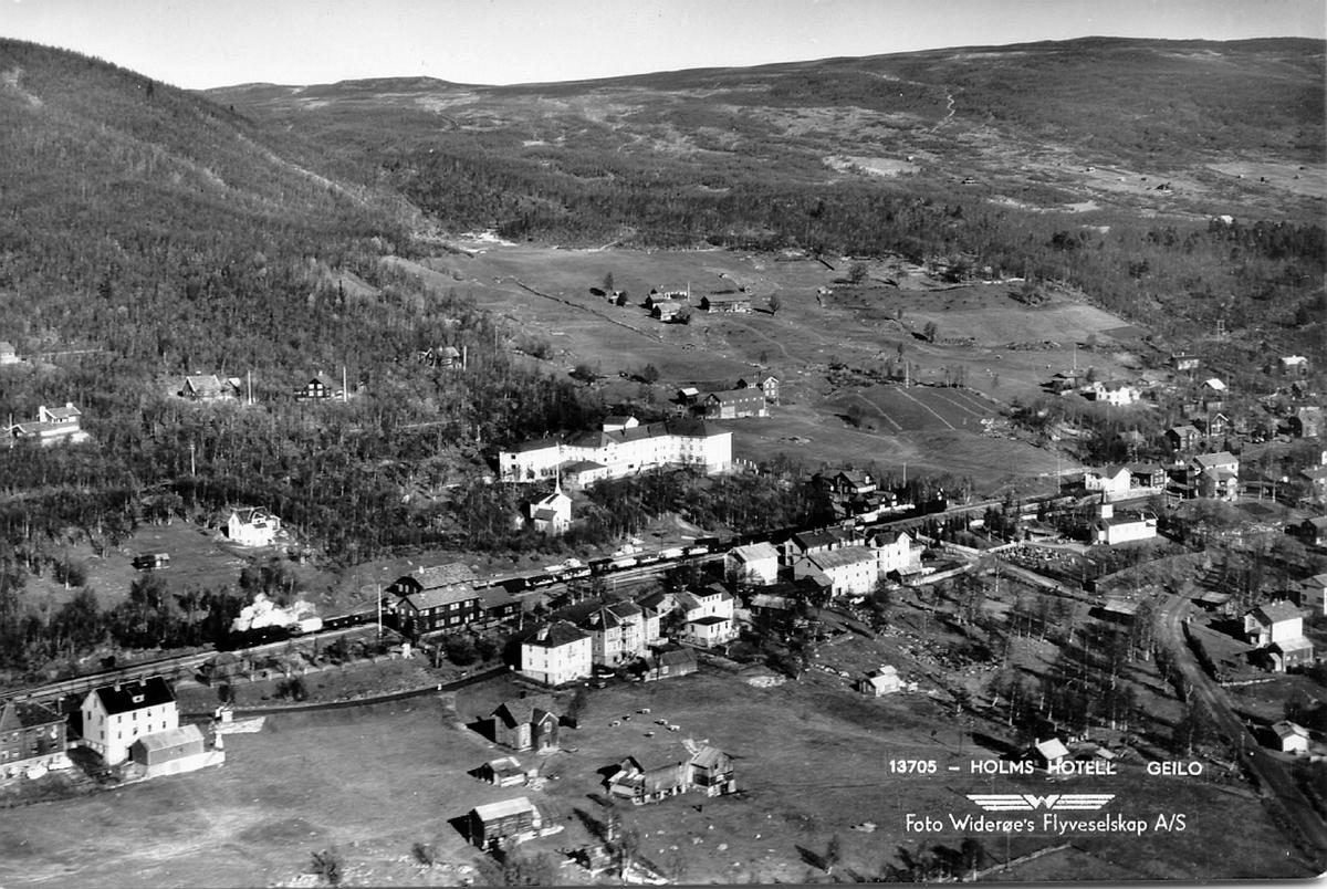 Flyfoto fra Geilo sentrum. Et godstog retning Bergen, trukket av damplokomotiv, står på jernbanestasjonen
