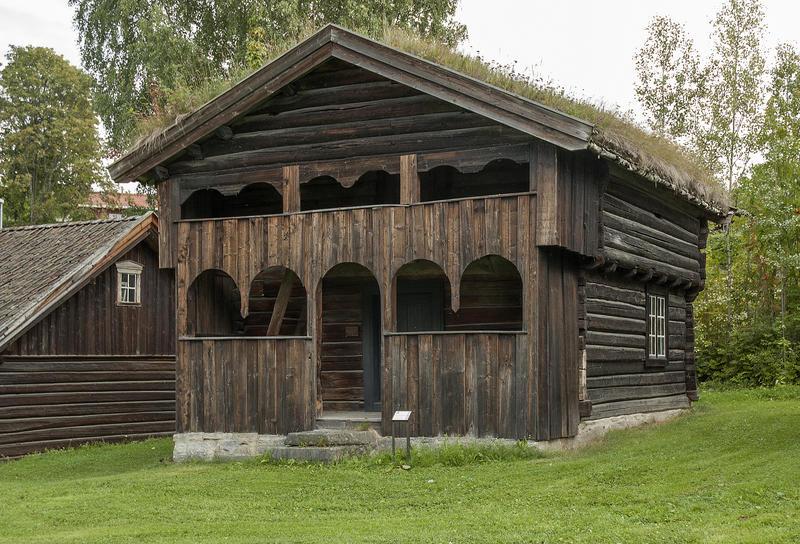 Toetasjers, relativt liten tømmerbygning med torv på taket og svalgang i to etasjer med buede åpninger. (Foto/Photo)