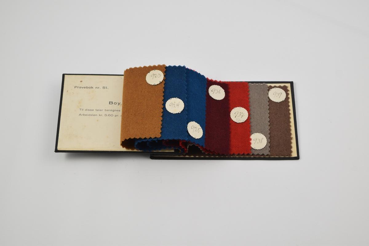 Prøvebok med 7 prøver. Tynne ensfargede ullstoffer. Alle stoffer er merket med en rund papirlapp festet med metallstifter hvor nummer er påskrevet for hånd.  Stoff nr. 923 (okergul), 924 (blå), 925 (blå-grønn), 936 (mørk rød), 937 (rød), 938 (grå), 939 (brun).
