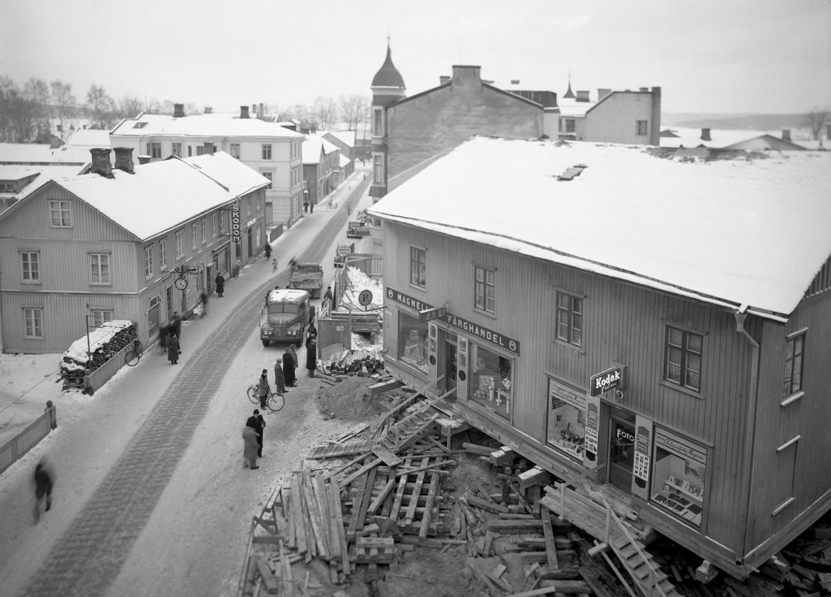 En affärsfastighet längs Kyrkogatan vrids och flyttas en bit ner på Hantverksgatan i oktober 1953.