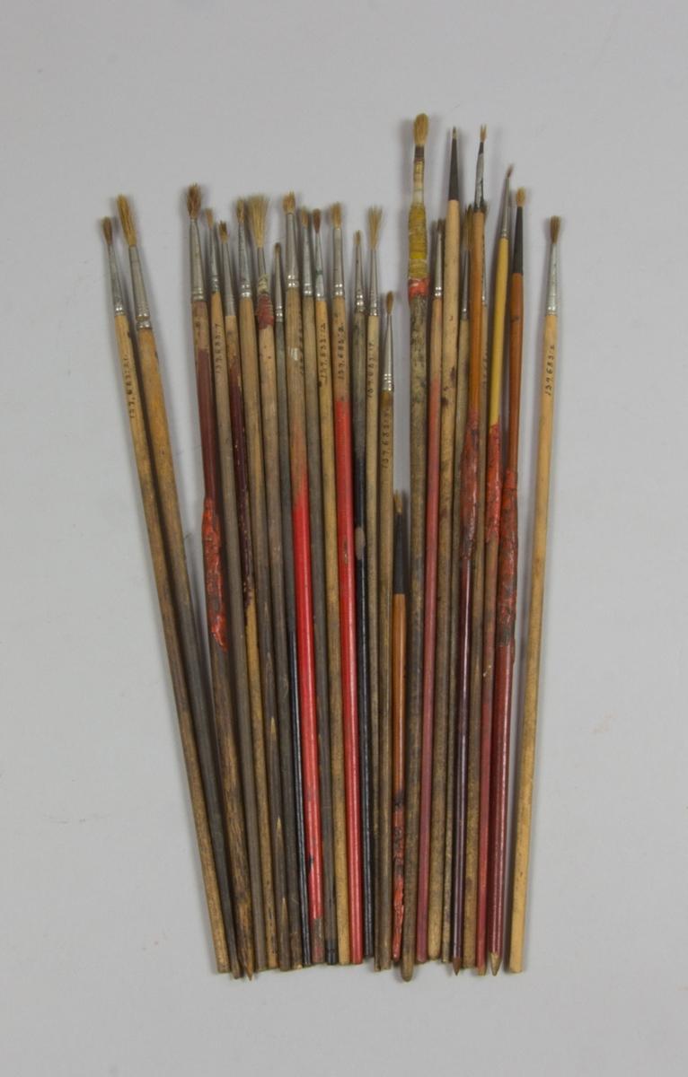 Penslar, 25 st, av något varierande längd. Träskaft och hylsor av metall samt borst.