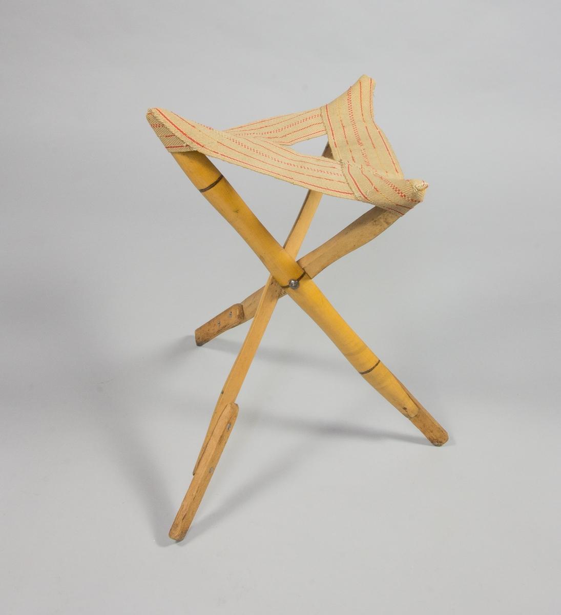 Trebent stol, pall. Hoppfällbar. Ben av bambu, nedtill förstärkta med trä. Trekantig sits av naturfärgad sadelgjord med röda ränder.
