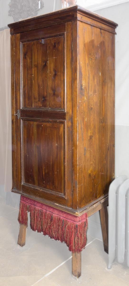 Skåp, verktygsskåp, av betsad furu, stående rektangulärt med dörr och fyra hyllplan. Dörren har utvändigt profilerade lister. Krönlist. Nyckel och profilerad nyckelskylt av metall. Skåpet står på ett fyrbent underrede av trä.