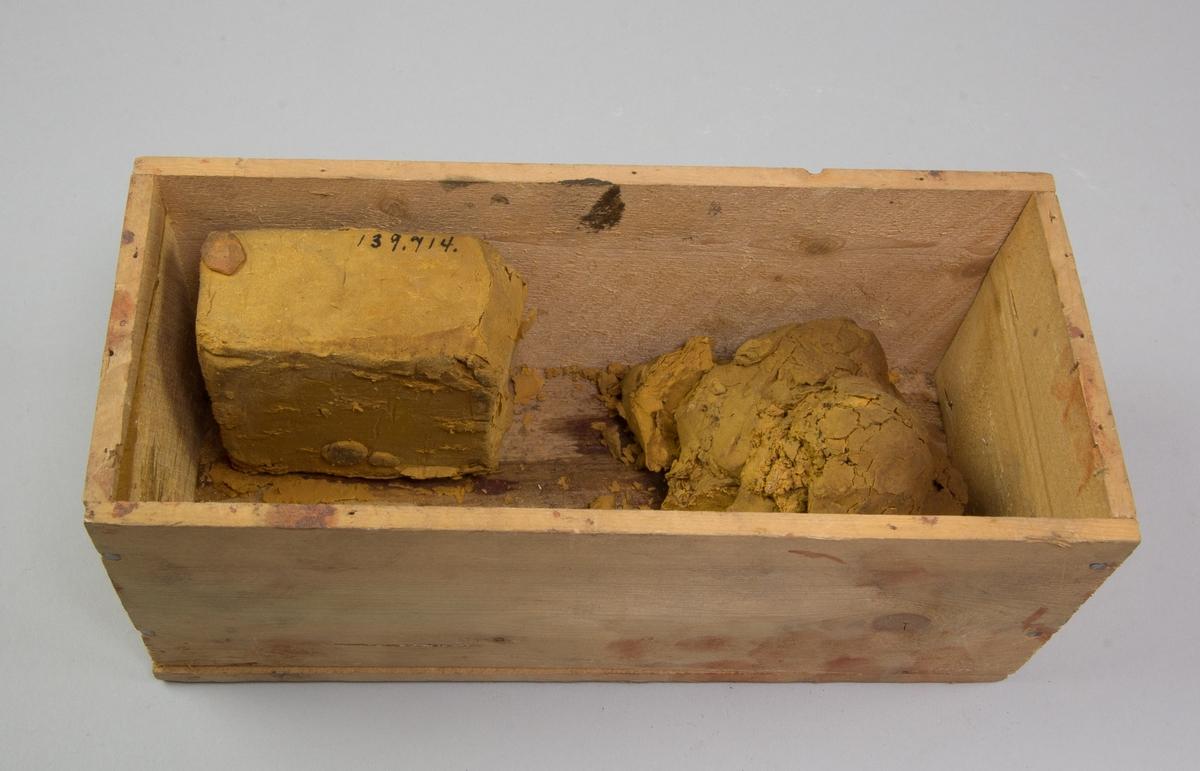 Låda av trä, rektangulär, utan lock. I lådan två stora klumpar av ockrafärgad plastelina, delvis sönderfallande.