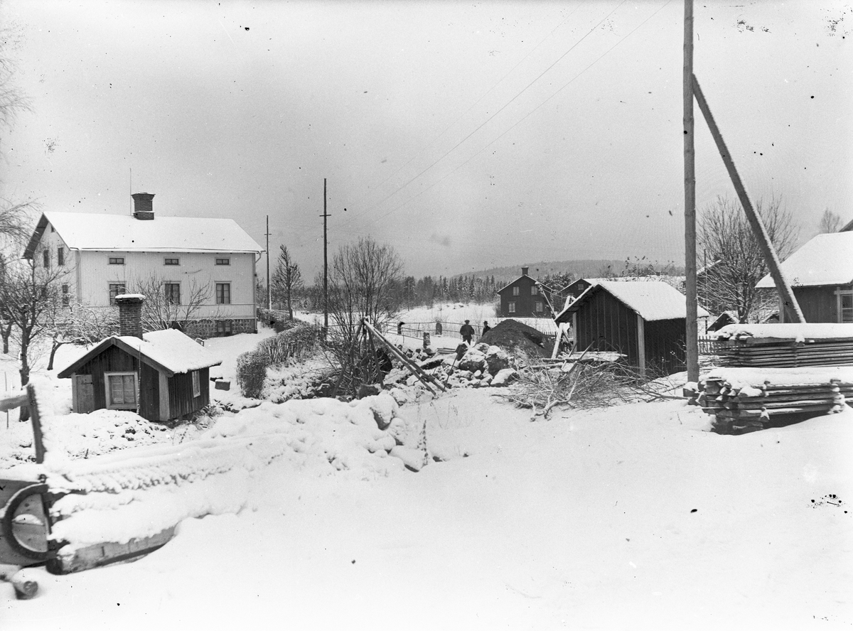 """Ågrävningen startade hösten 1927. Från Sjutängsvägen i sydost med gamla bron i centrum. Byns spruthus i förgrunden flyttades till renseriplan. Åsmundshyttan nr. 5 """"Jan-Mats"""" lilla gård och tvättstuga och till vänster Åsmundshyttan nr. 6 """"Mattsas"""" i bakgrunden"""