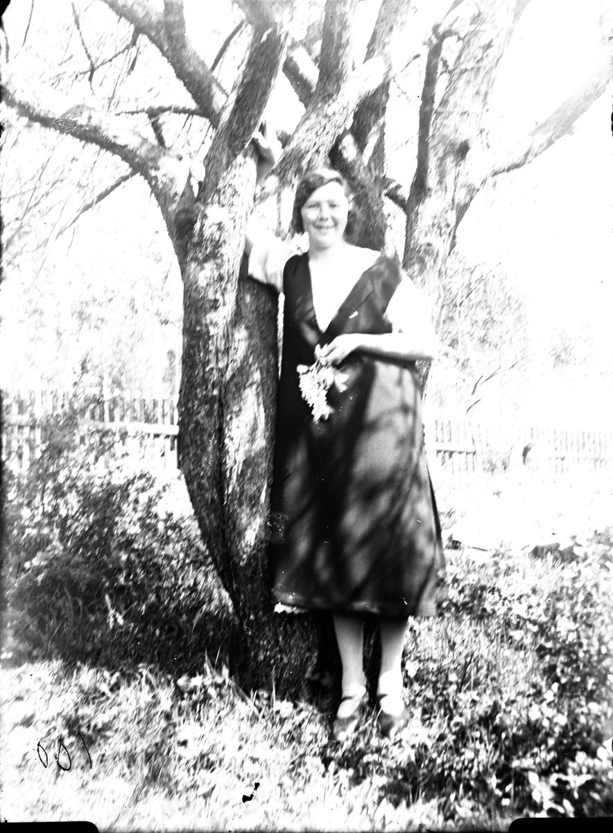 Kvinna vid träd.