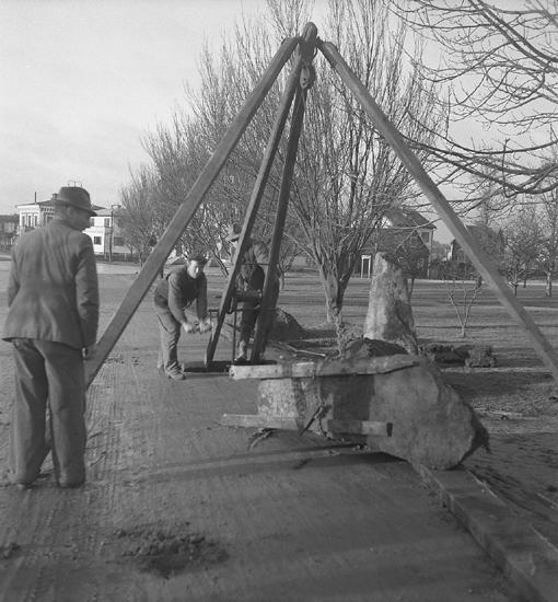 Foto från arbetet med att flytta runstenar vid Aringsås kyrka.Tre män är sysselsatta vid en s.k. stenjätte. I förgrunden ligger en omkullvält runsten. I bakgrunden skymtar några bostadshus. Flyttning av runstenar vid kyrkan, 1940.12.
