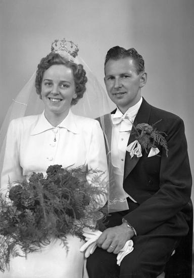 Foto av ett okänt brudpar. Hon är klädd i vit brudklänning med slöja och stor, gammaldags brudkrona. Han är klädd i frack.Knäbild. Ateljéfoto.