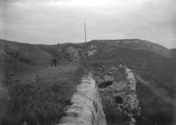 Foto av de gräsbevuxna fästningsvallarna. I bakgrunden syns