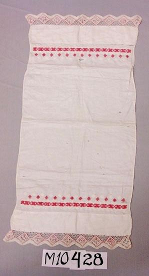 Avlång duk av vit lärft, vid kortsidorna breda fållar med knypplad spets  som har infällt rött garn (larmgarn). Korssömsbroderi i rött och vitt. Fållens br: 60 mm. Spetsens br: 40 mm.  Inskrivet i huvudkatalog 1939 Funktion: Duk för byrå eller skänk.