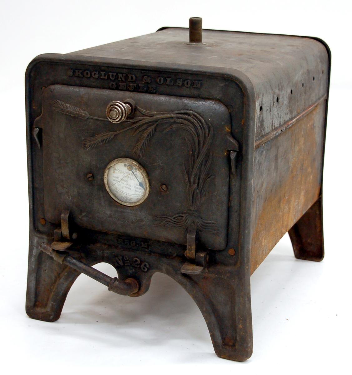 """Acc.kat: Gasugn.Gjuten, rektangulär med rundade överkanter. Lucka med termostat, märkt: """"SKOGLUND & OLSON, Gefle. REG.M.No 26"""". Veteax utgör dekor på luckan."""