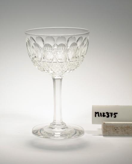 """Glas tillhörande servis """"Douglas"""". (K 142). Dekor bestående av skär, oliver och facetter. Ofärgat klarglas. Ovan angivna mått avser fotens diameter. Inskrivet i huvudkatalogen 1942.  Kataloger: Se 1896 och 1904 års kataloger. Funktion: Glas"""