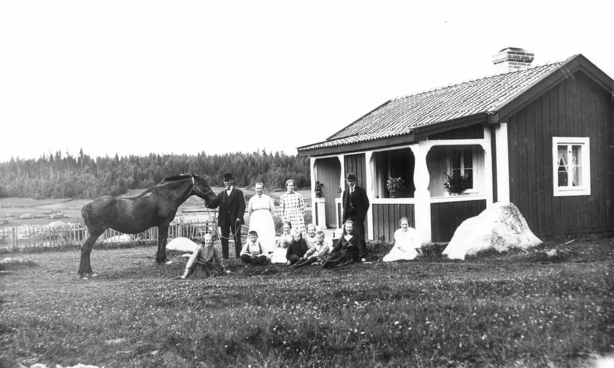 Familj samlad framför sitt hus.