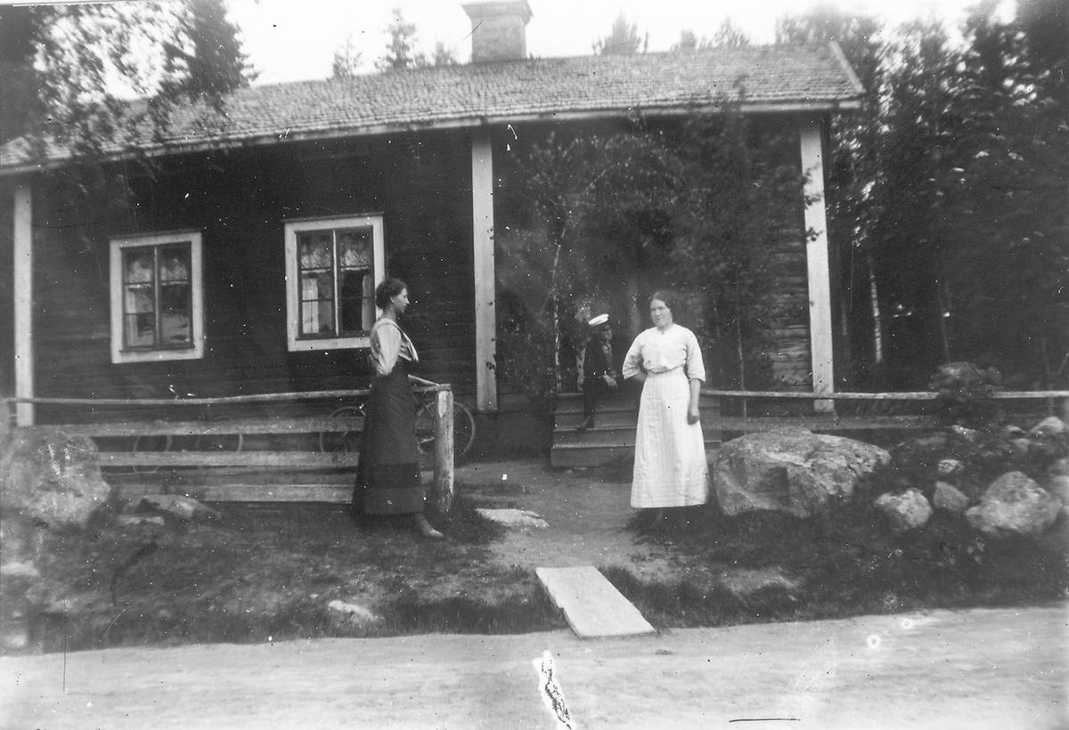 Fotografen Per Lindbergs hem i Järvsö. Kvinnan till vänster är Ester Lindberg, mannen på bron Jonas Lindberg (Per Lindbergs bror) och kvinnan till höger Anna Eugenia Henriksdotter, född 1 aug 1894 (gift Larsson), adoptivdotter till Jonas Lindberg.