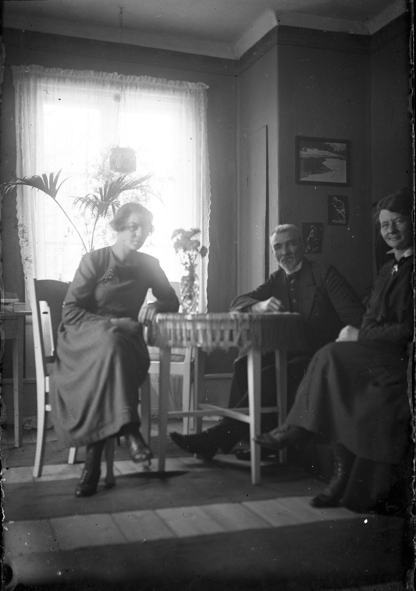 Tre personer vid bord.