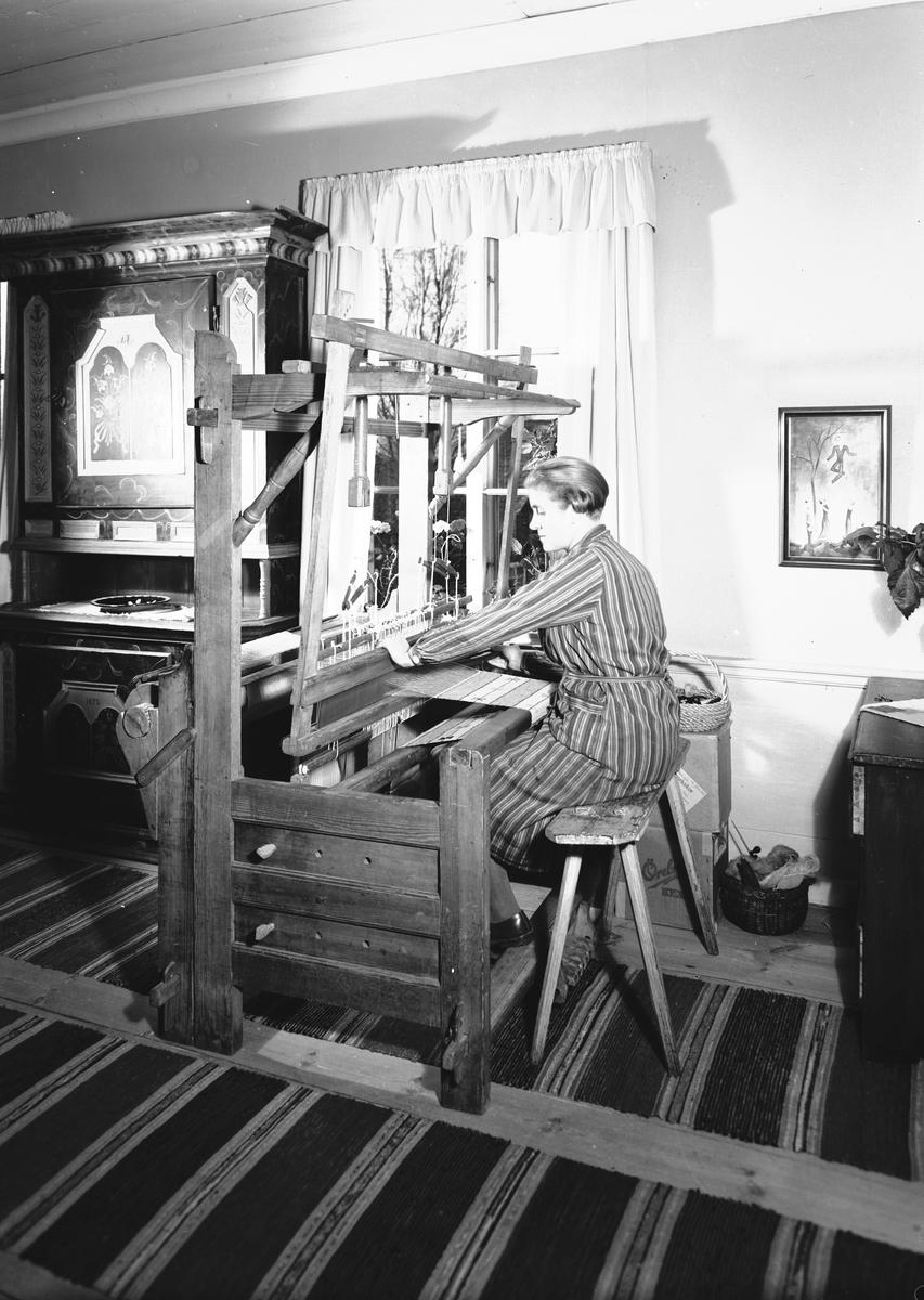 """Från boken """"Svenska Hem i ord och bilder"""" från 1944. Hemma hos Konstnären Manne och Brita Östlund, ägare till Jons i Västbyggeby. Fru Brita Östlund vid vävstolen. Till vänster ett mörkblått Järvsöskåp med röda speglar från 1825."""