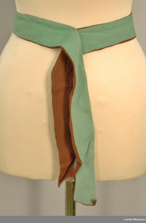 Kjolen er satt saman av ein bluse og ein kjole. Kjolens fason; (seleskjørt med bluse inni). 6 trekte knapper foran frå halsen. Det kneppes med trykknapper. Ermene er rynket ved skuldrene. Ingen krage men 2 snipper foran. Kjolen er litt utskrådd nede, avdelt i livet, åpning i siden - trykknapper. Løst knytebelte høyrer med - En side grøn, den andre brun.