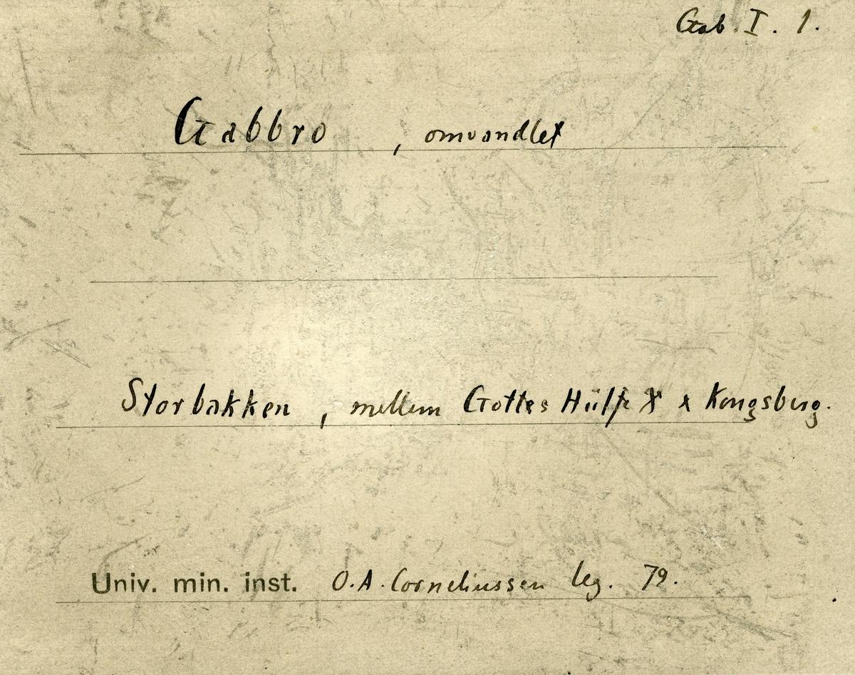 To prøver. To etiketter i eske:  Etikett 1: Gabbro «Storbakken» mellom Gottes Hülfe Gr og Kongsberg OAC 79  Etikett 2: Gab. I.1 Gabbro, omvandlet Storbakken, mellom Gottes Hülfe Gr og Kongsberg O.A. Corneliussen leg. 79