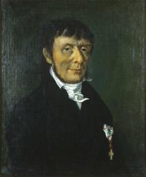Portrett av Carl Stoltenberg. Mørk drakt, hvit skjorte og halsbind. Orden på venstre side av brystet.