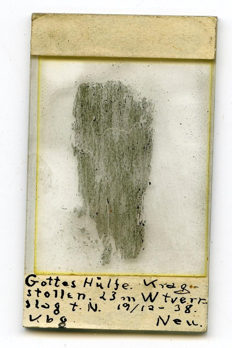 Tre prøver og ett tynnslip  Etikett i eske: 23 m. v. fra tverslaget i ort t. v. G. H.  På tynnslip: Gottes Hülfe Kragstollen. 23 m W tverrslag t. N. 19/12-38 Kbg Neu 19/12 1938