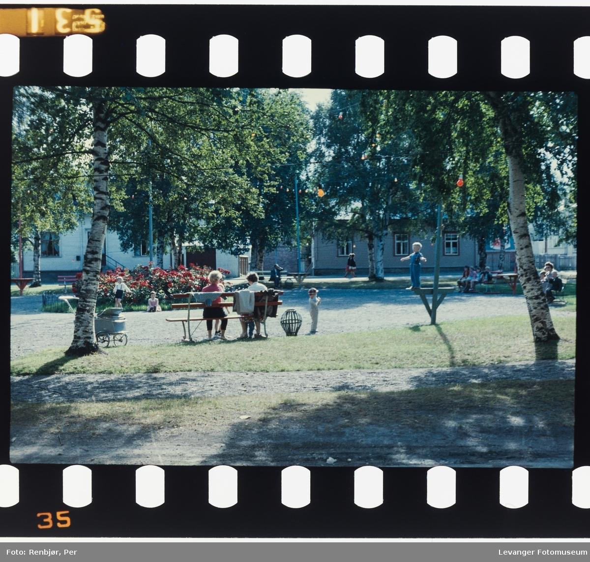 Barn leker i parken, mens de voksne prater.