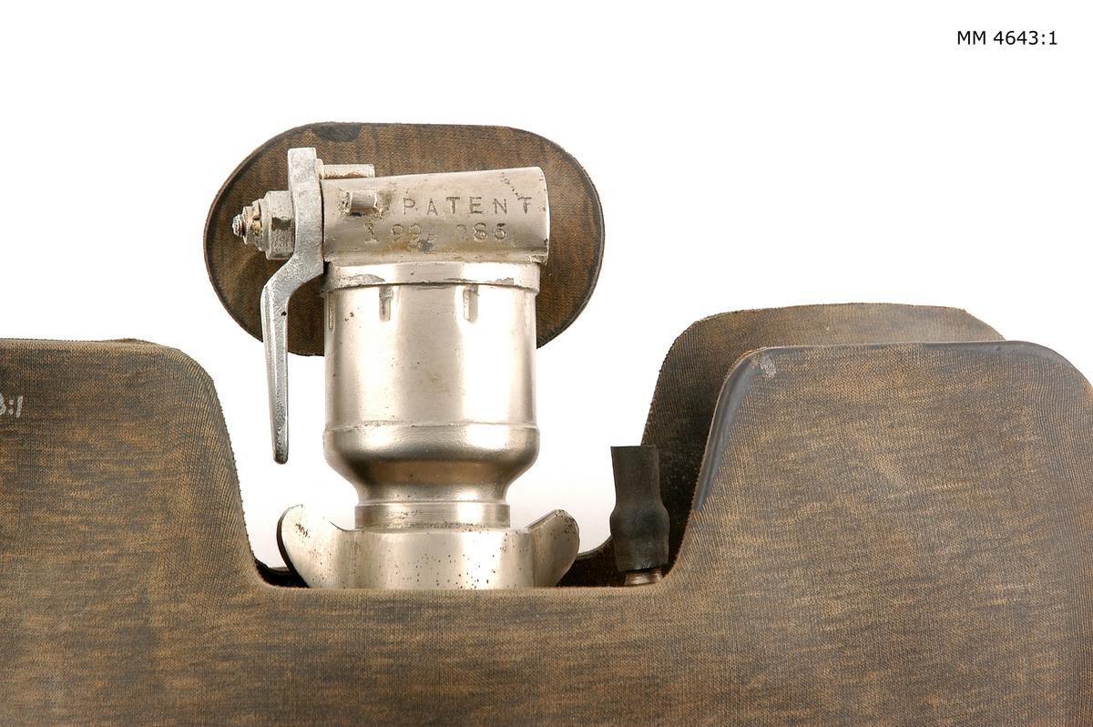 """Andningsapparat, andningsväst, M/40 """"Momsen"""". Material: gummi med ventiler av mässing, förnicklade. Apparaten invändigt försedd med behållare, utvändigt med söljor och vidhängande band av bomull för påsättning runt hals och liv samt galvaniserad kätting med fjäderklämmor. Andningsventilen märkt: Patent 1999086. Apparaten förvaras i påse av rödbrun duk, dimensioner: 400 x 480mm."""