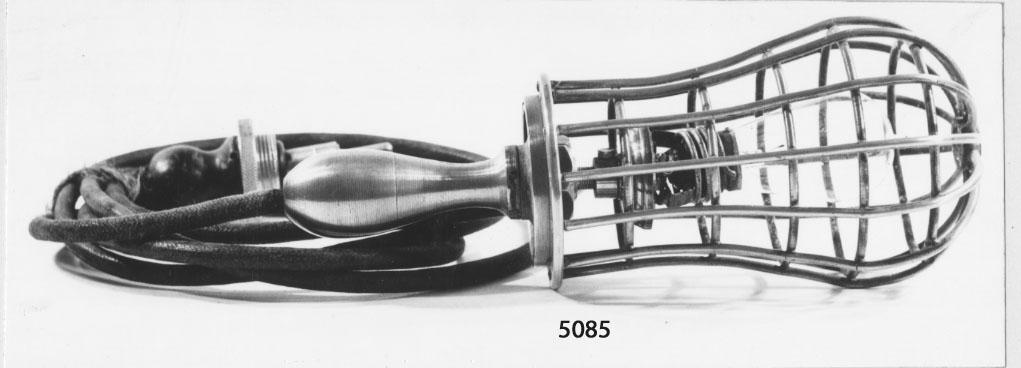 Lampa, skaft-, elektrisk. Har tillhört kanonbåten Skuld. Försedd med galler och el. sladd med stickpropp.