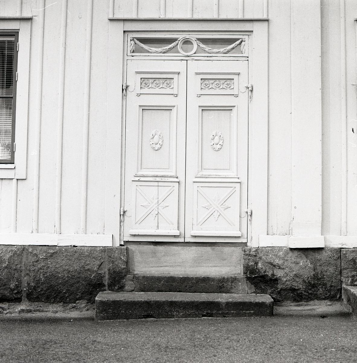 Någonstans i Hälsingland finns denna praktfulla port med dubbeldörrar. Portarna är indelade i tre fält med olika former av snideriutsmyckning. Längs upp sitter ett överljusfönster med snidade trägirlanger som ormanent. En stentrapp leder upp till dörren.