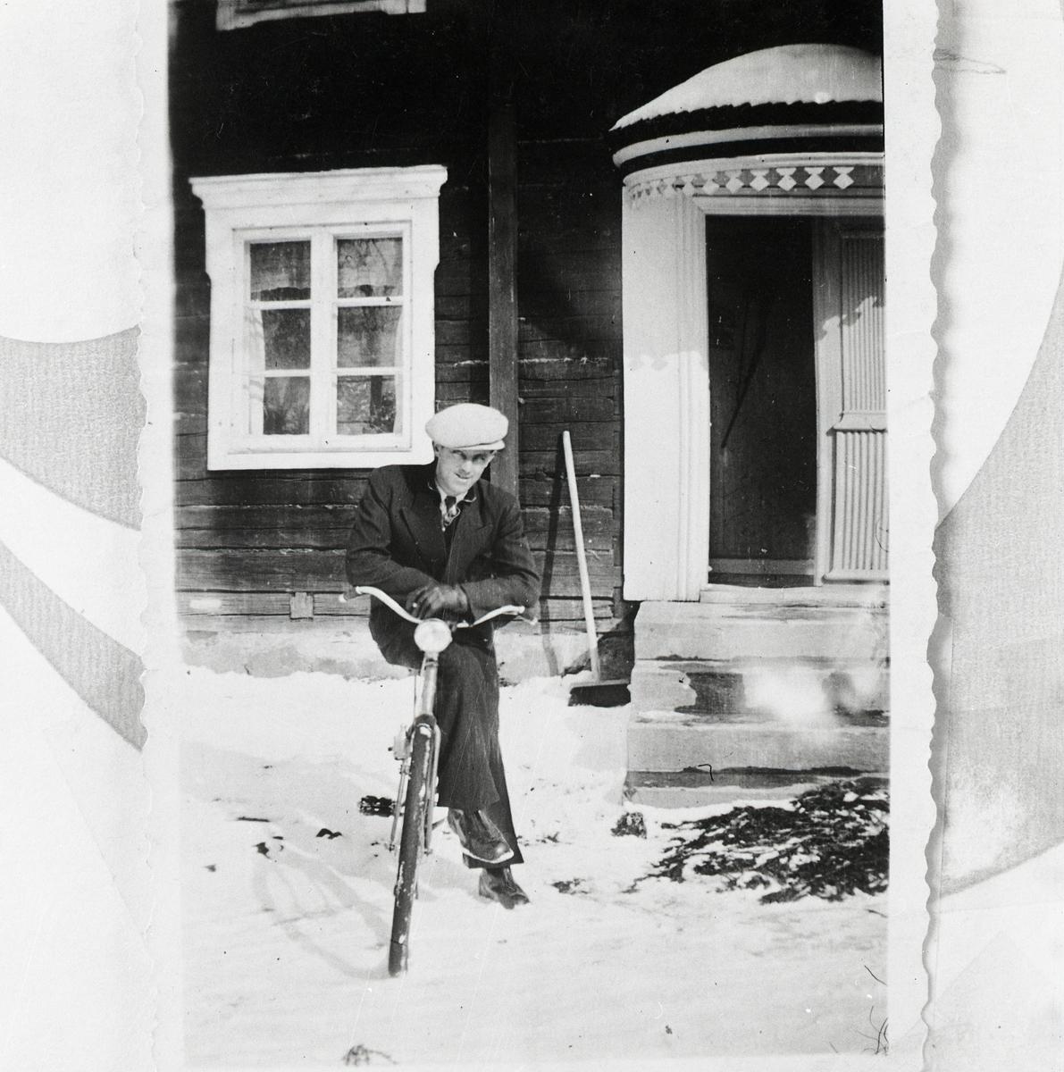 Framför ett hus sitter en man framlutad på en cykel. Han bär keps, kostym och läderhandskar. Brokvisttaket och marken är täckta av snö och lite granris är utlagt framför trappan.