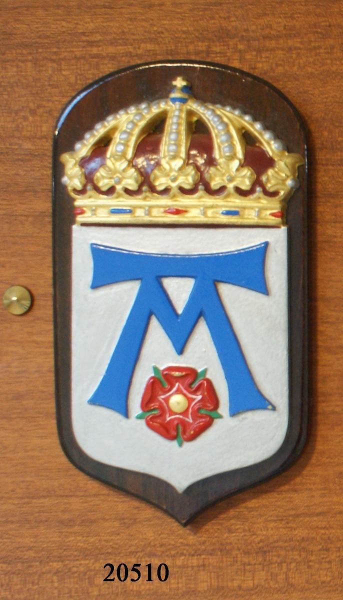 Vapensköld gjuten av mässing. Krönt med kunglig krona, målad i heraldiska färger; guld, silver blått och rött. Bottnen i silver är försedd med emblem i blått format format som ett M med en balk över. Nedanför emblemet finns en röd blomma med fem kronblad. Guld i mitten och gröna småblad mellan kronbladen. Skölden är fäst till en fernissad platta av mörk mahogny.